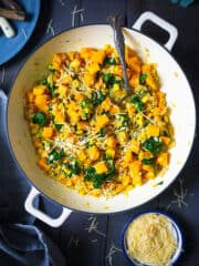 An overhead shot of barley risotto with butternut squash in a dark background