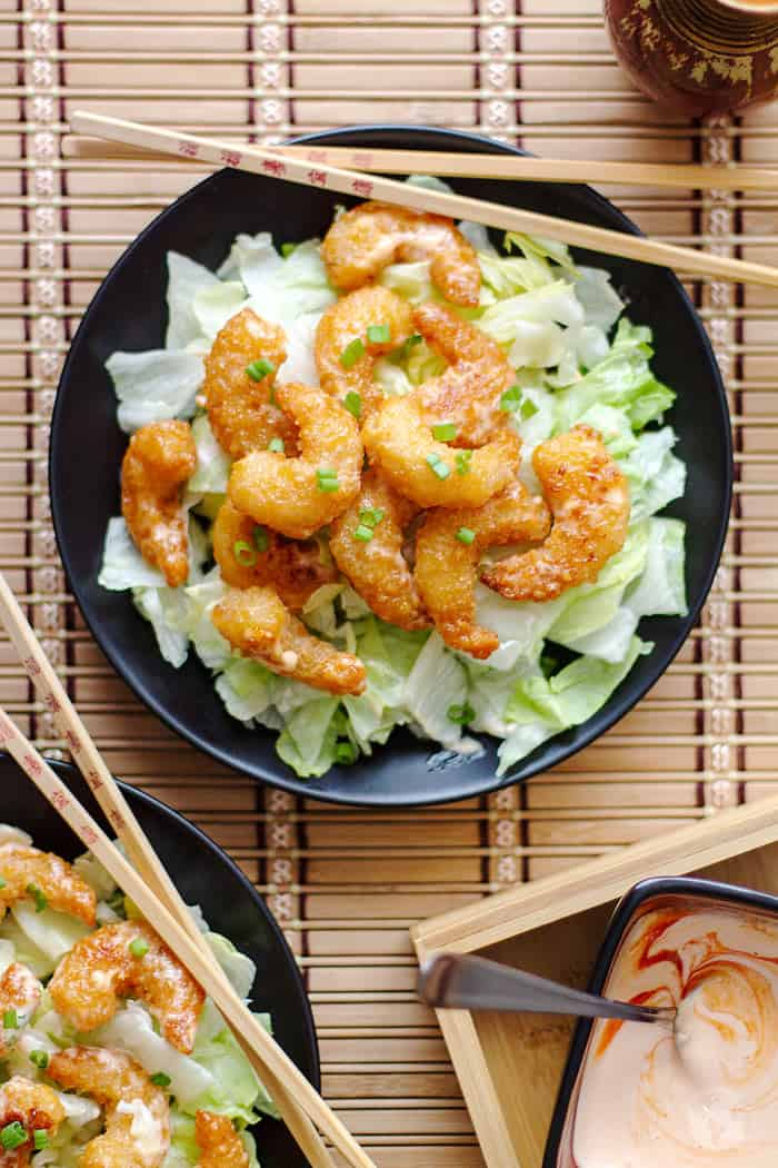 overhead shot of shrimp with bang bang sauce on a black plate and bamboo background