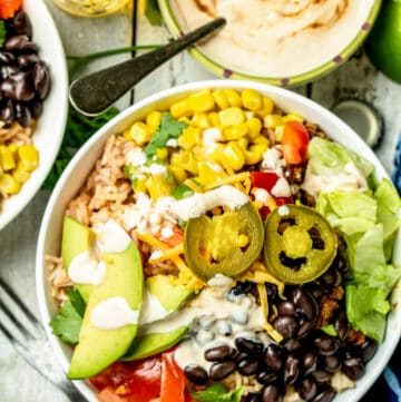 An overhead shot of assembled burrito bowl topped with avocado, jalapenos, black beans, corn, tomatoes, peppers, and lettuce.