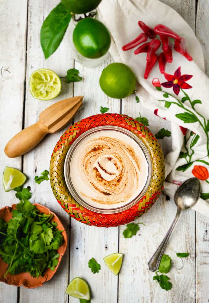 Overhead shot of chipotle burrito sauce in a red bowl with ingredients around it on a white rustic wooden board.