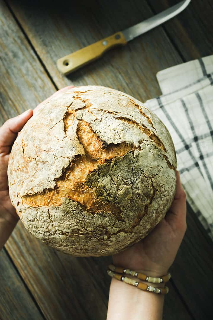 A flat lay of hands holding the artisan bread over the wooden background.