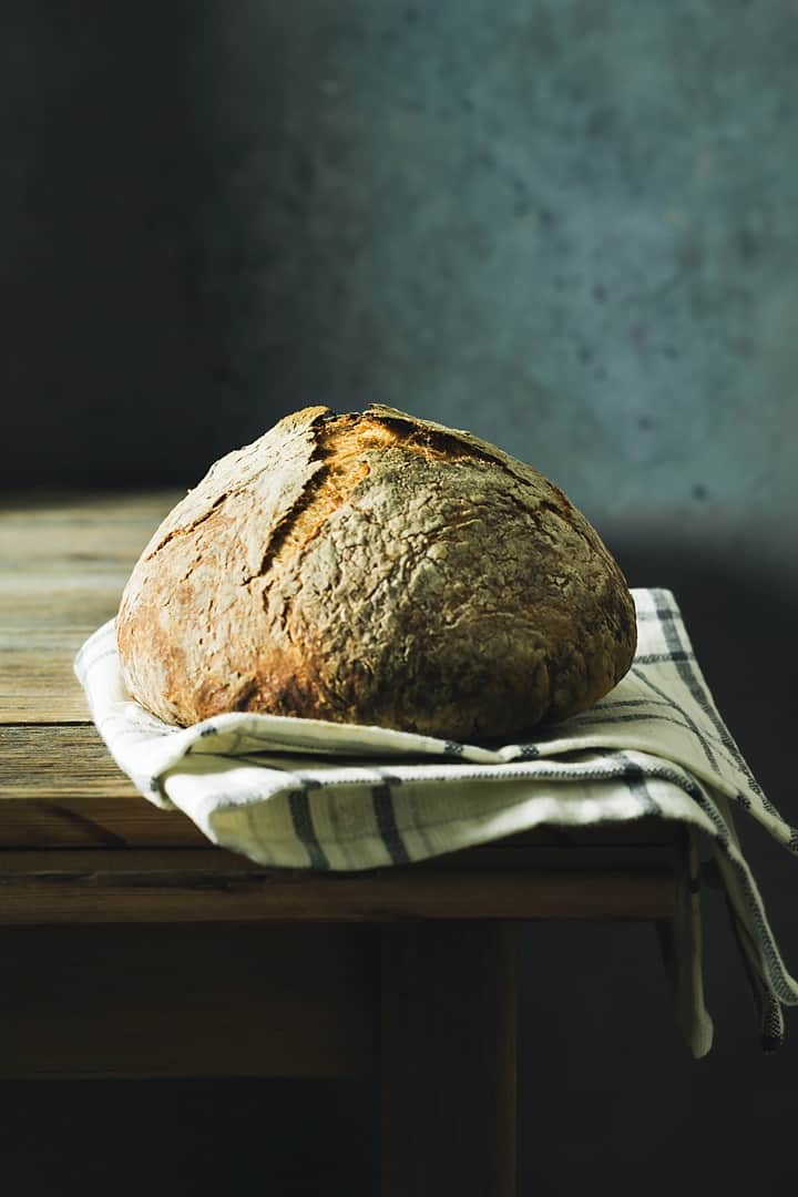 Straight-on shot of baked bread loaf on a kitchen towel, sitting on a rustic wooden table
