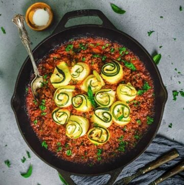 An overhead photo of cast-iron skillet with zucchini rolls in meat sauce on a gray background and dark gray towel.