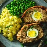 An overhead of meatloaf slices with smashed potatoes and peas on a gray plate.