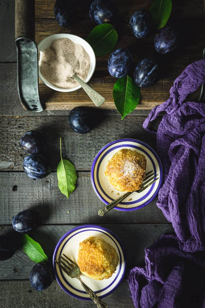 A flat lay of two dumplings on small plates with a bowl of cinnamon sugar, fresh plums, and purple cloth on a gray wooden background