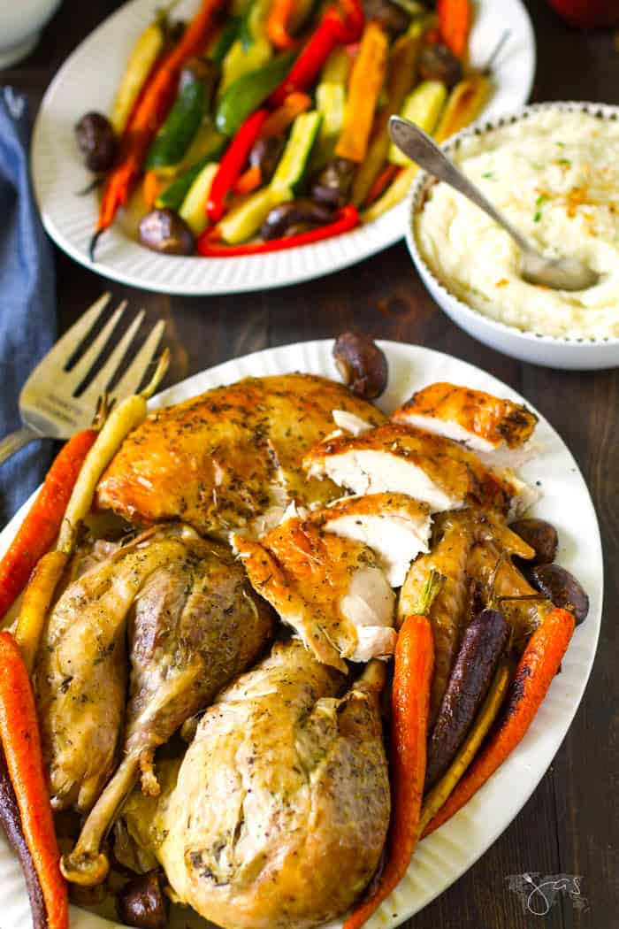 An overhead shot of carved turkey with roasted vegetables and mashed potatoes in the background.