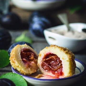 A front shot of the plum dumpling sliced in half with plums and sugar dish in the background