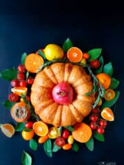 An overhead shot of fillo bundt in the middle of fruit and veggie wreath on a dark background