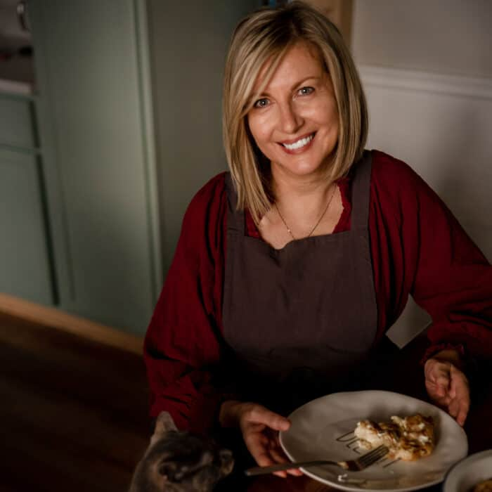 A woman sitting at the kitchen table with a plate of food.