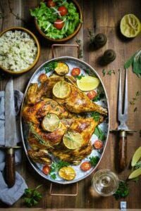 An oval dish with roasted whole chicken with lemon slices and fresh herbs sitting on a wooden table with cutlery and side dishes.
