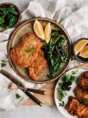 A plate with breaded meat, greens and lemons on a rustic table