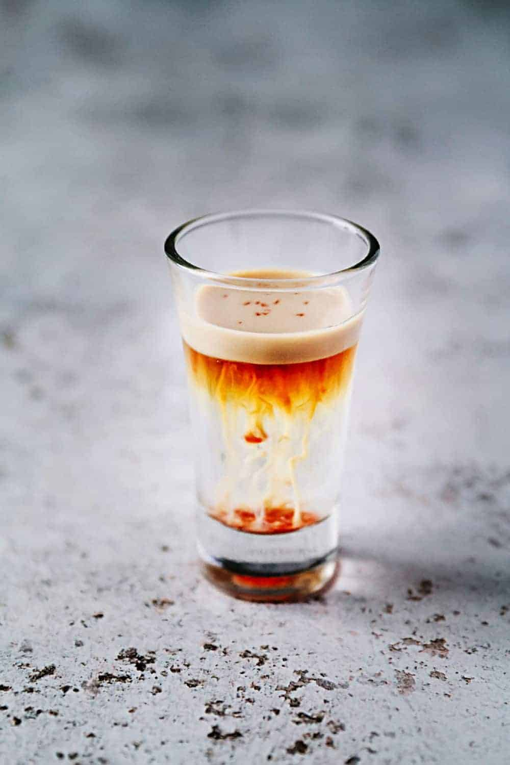 A small shot glass with jellyfish beverage sitting on a gray counter