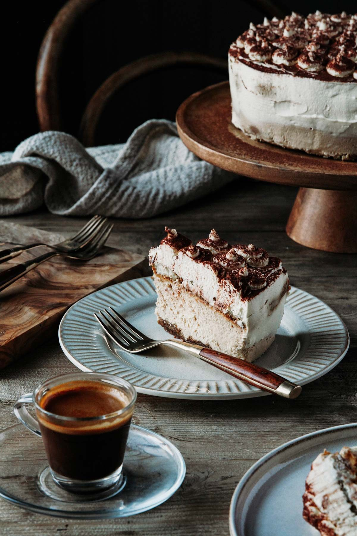 A slice of tiramisu cheesecake sitting on the plate with espresso coffee and more cake
