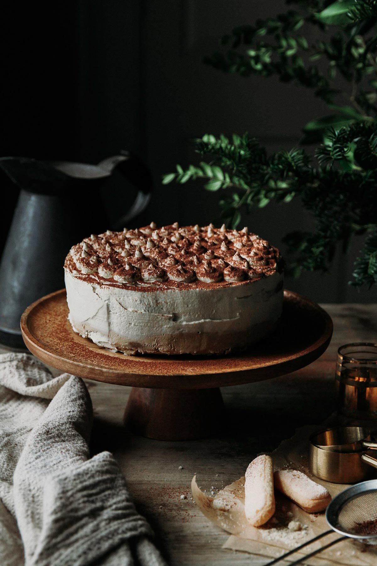 Tiramisu cheesecake on a cake stand with kitchen towel on a rustic table