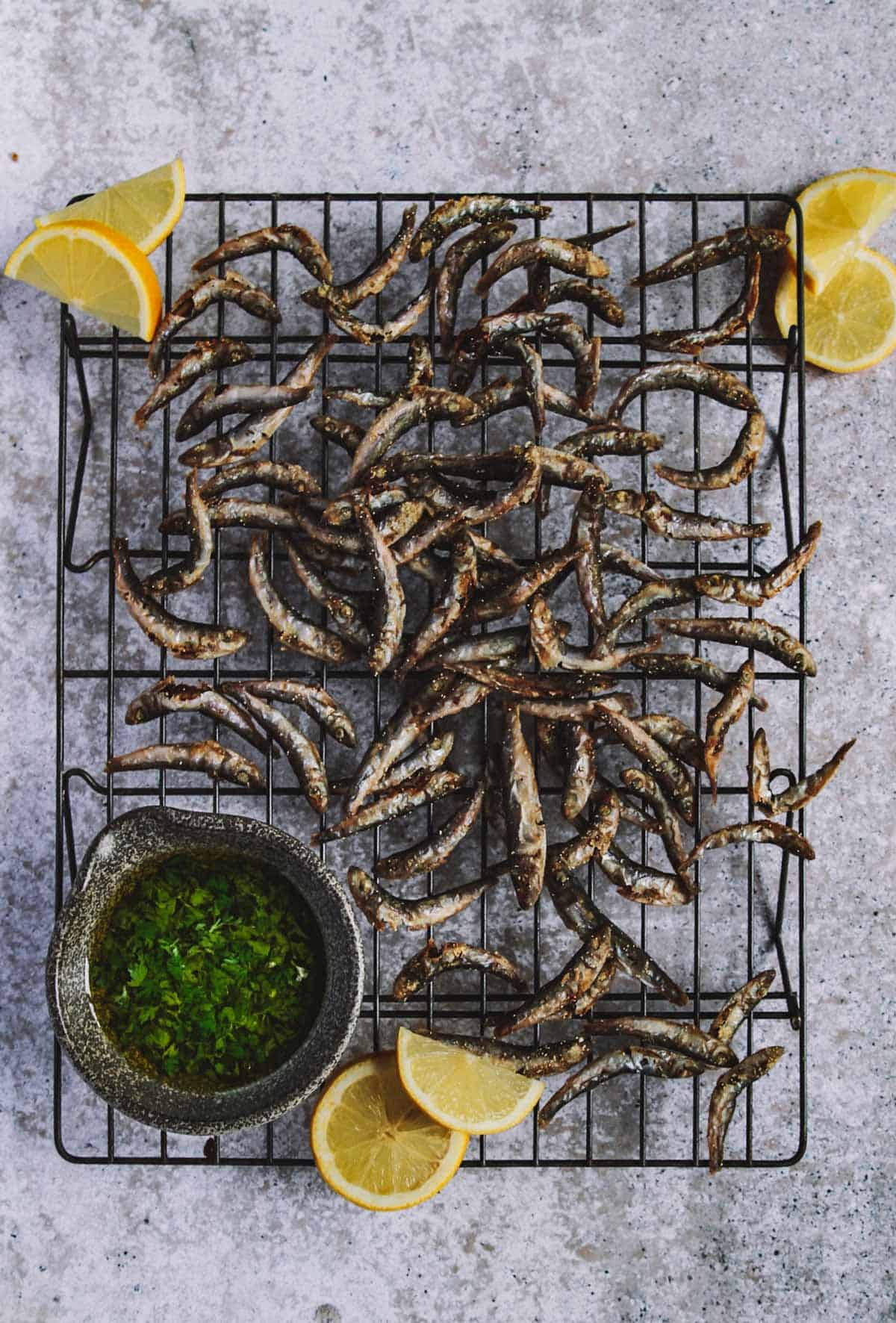 A cooling rack on a table with small fried fish, lemon slices and a bowl with sauce.
