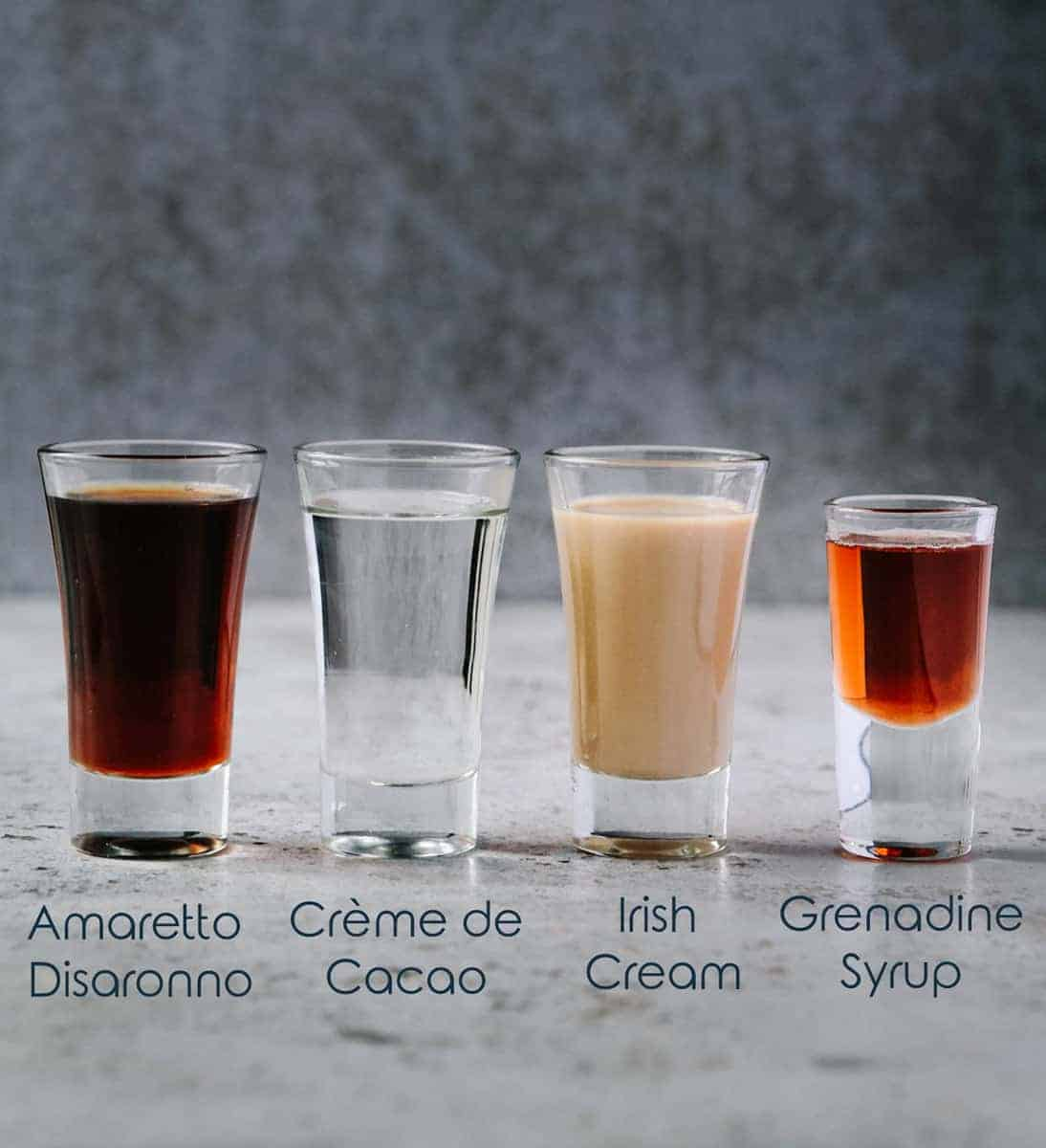 Four small glasses with different alcohol ingredients for jellyfish shot
