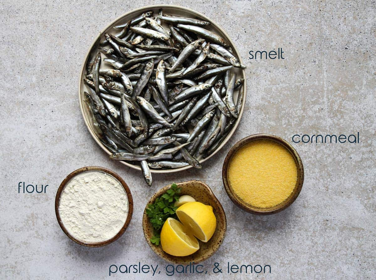 A plate with fresh smelt and small bowls with flour, cornmeal, and lemons