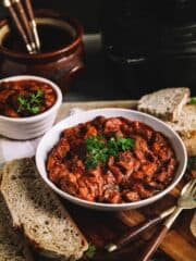 A lage and a small plaate of beef stew on a wooden table with bread and utensils