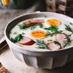 A bowl of white Polish creamy soup with boiled egg halves and kielbasa sausage.