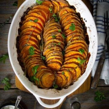 An oval dish with slices of crispy roasted sweet potatoes sitting on a table.