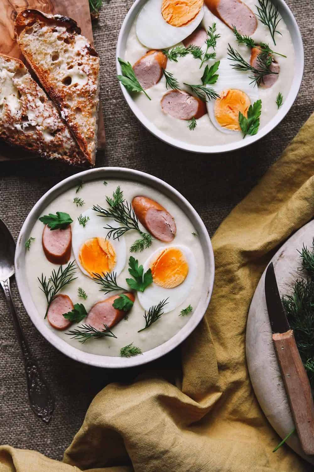 Two bowls of Polish bialy barszcz topped with hard-boiled eggs halves, sliced sausage, and fresh dill.