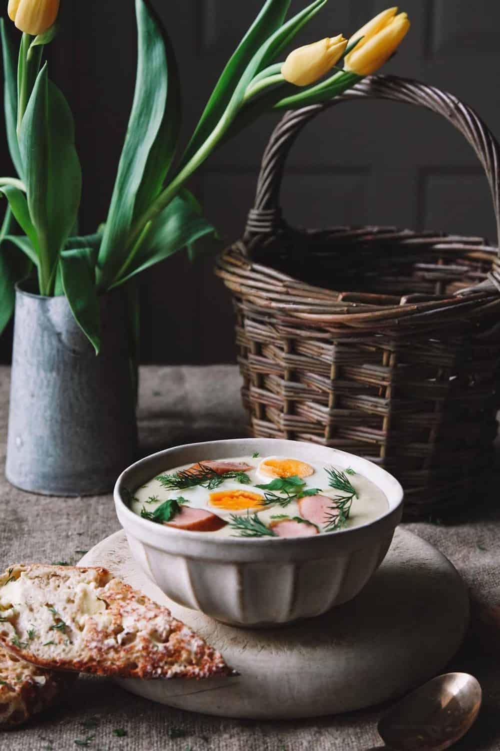 A bowl with Easter breakfast soup traditional to Poland on a table with a basket and tulips in a vase.