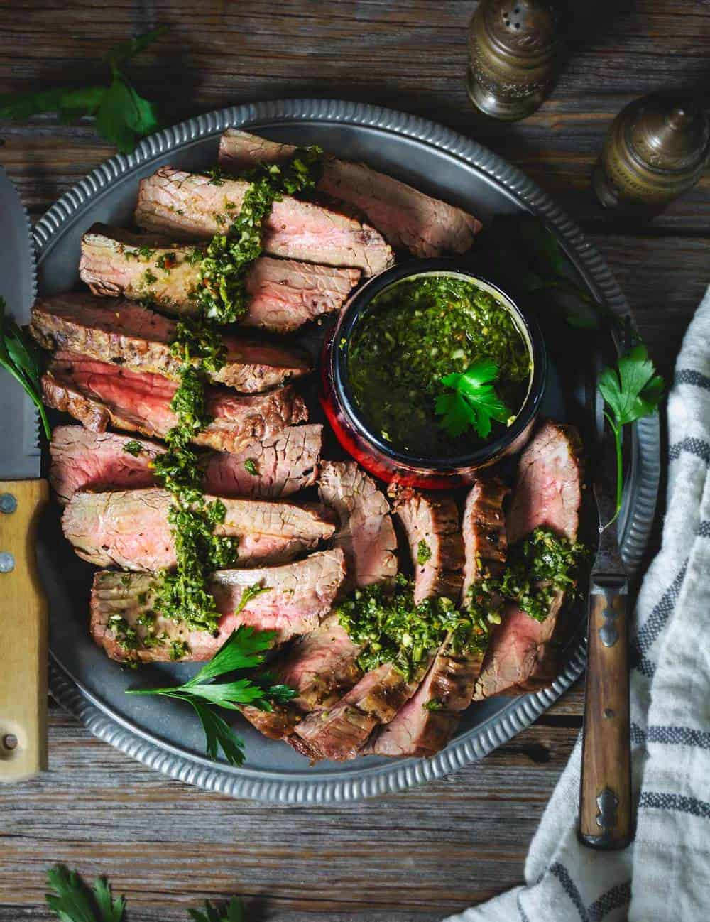 Slices of grilled steak ion a platetopped with chimichurri parsley sauce
