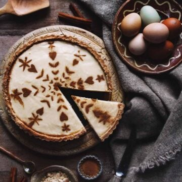 A rustic milk tart on a table with eggs, tablecloth, and cinnamon.