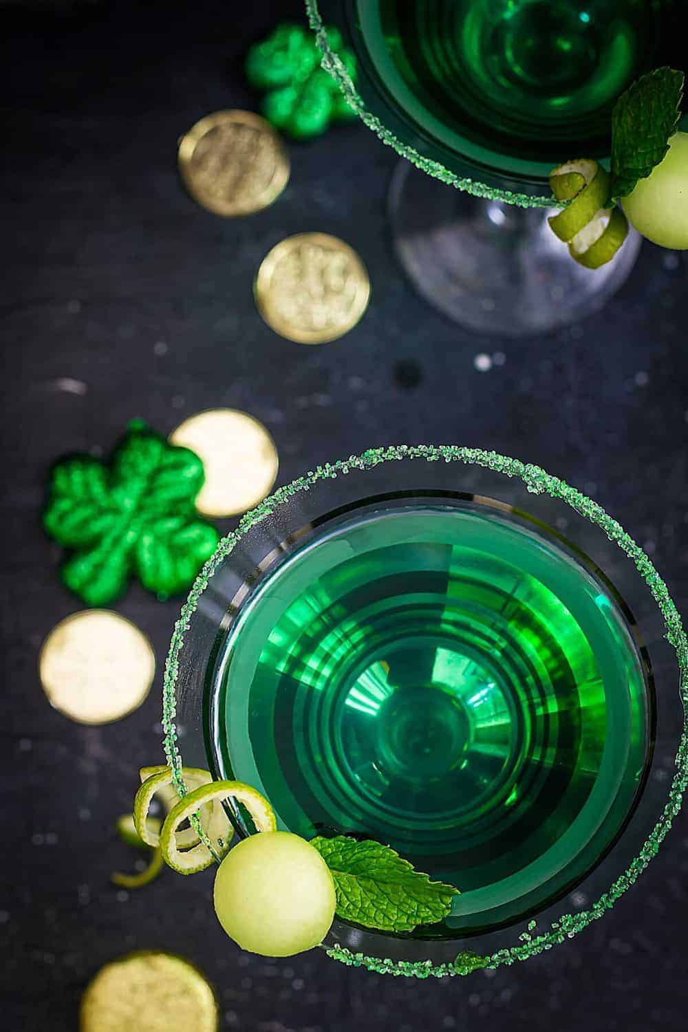An overhead view of two glasses with melontini drink on a black table with St. Patrick's Day decorations.