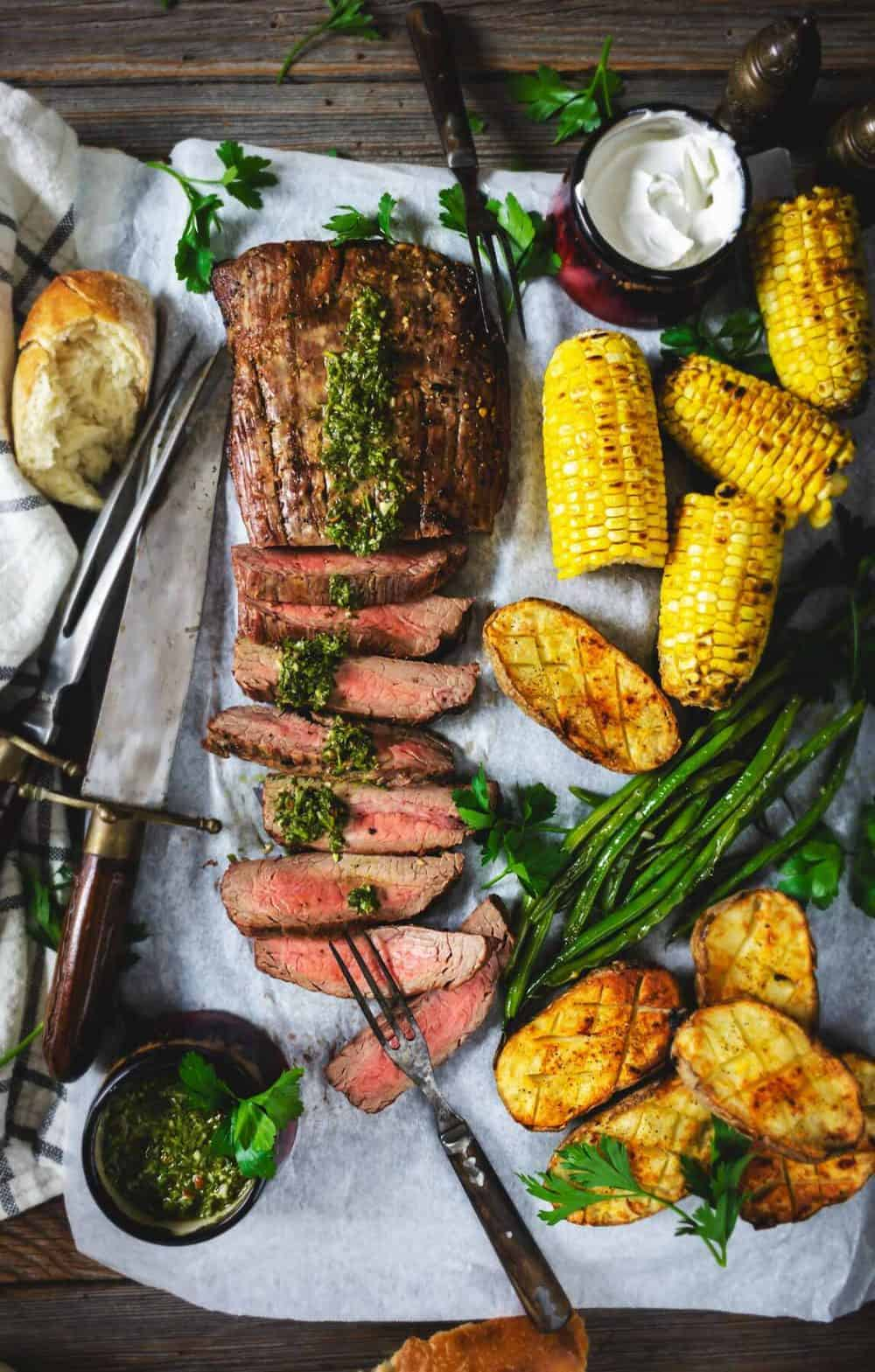 A flat lay of grilled steak with vegetables on a sheet pan