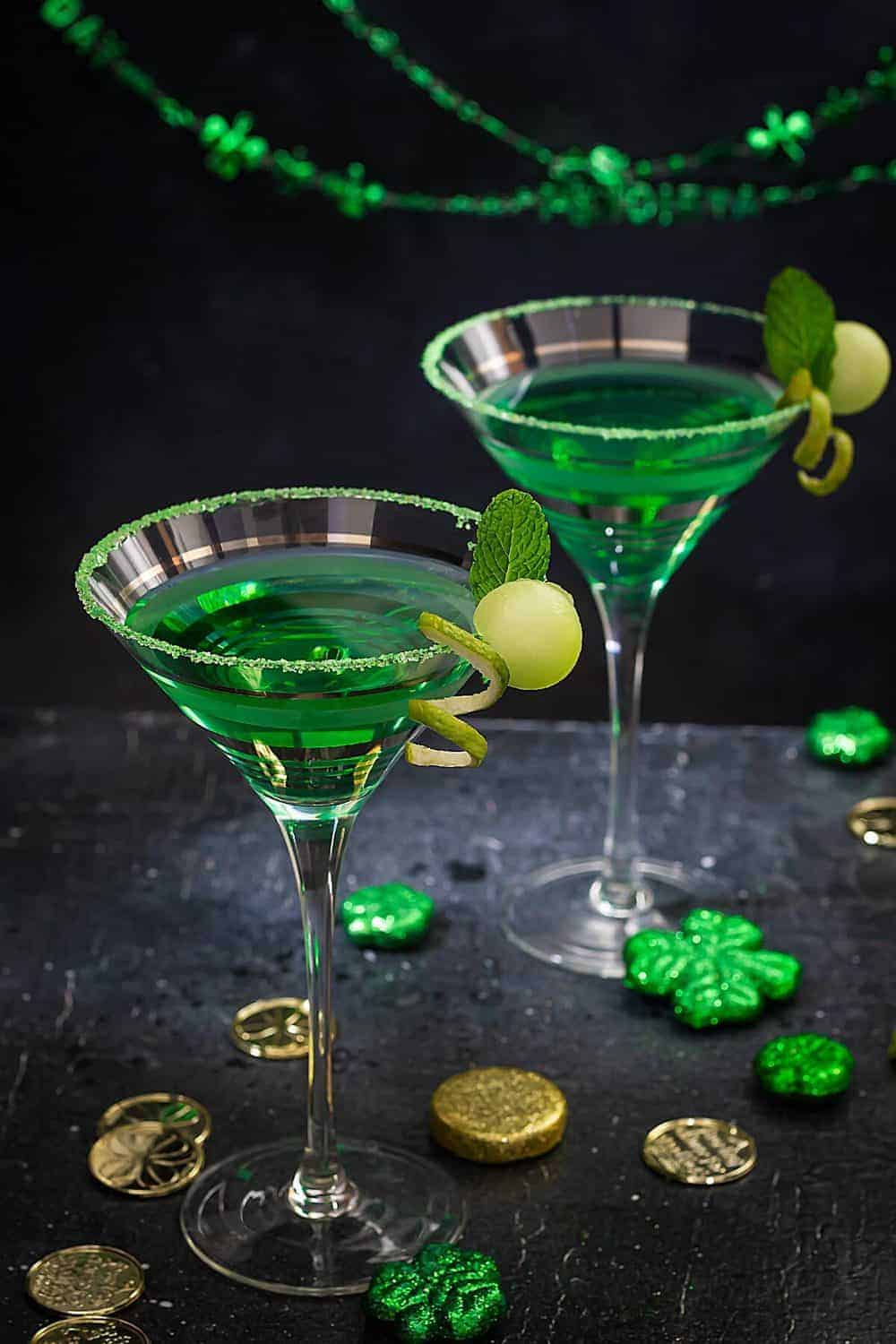 Two martini glasses with green cocktail on a black background.