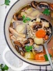 A close up of the krupnik soup with barley, mushrooms, and vegetables in a pot with a ladle.