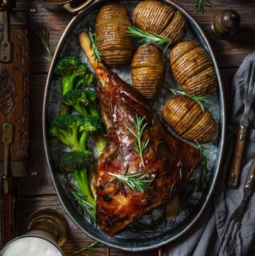 Finished recipe of lamb meat with beer on a metal roasting pan with potatoes and broccoli on a wooden table.
