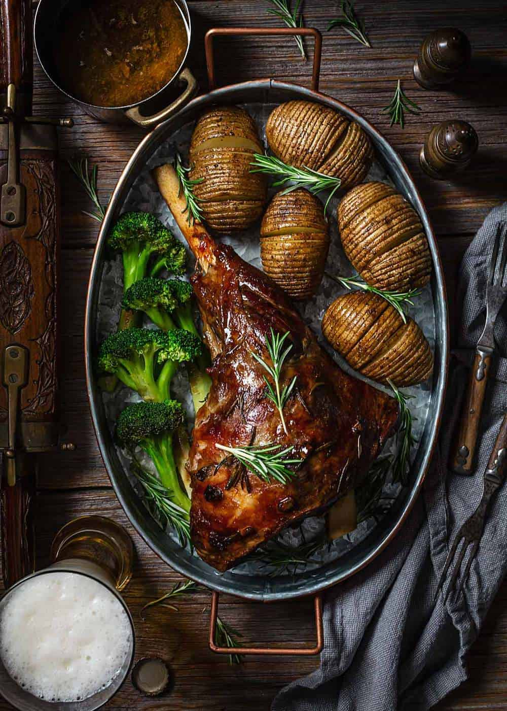 Slow roasted leg of lamb with beer on a metal roasting pan with potatoes and broccoli on a wooden table.