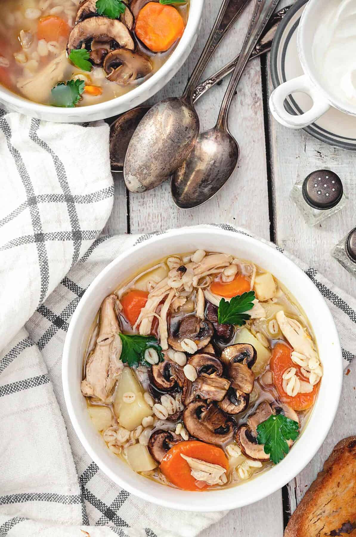 Two bowls of chicken barley soup on a white wooden table with towel and spoons.