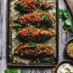 Lamb and pine nuts stuffed eggplant halves lined up on a baking sheet.