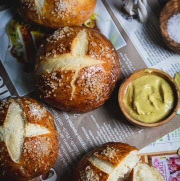 Overhead shot of pretzel rolls on a German papers with salt and mustard.
