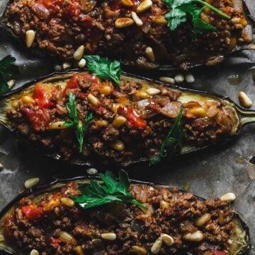 Three eggplant halves stuffed with minced lamb meat.