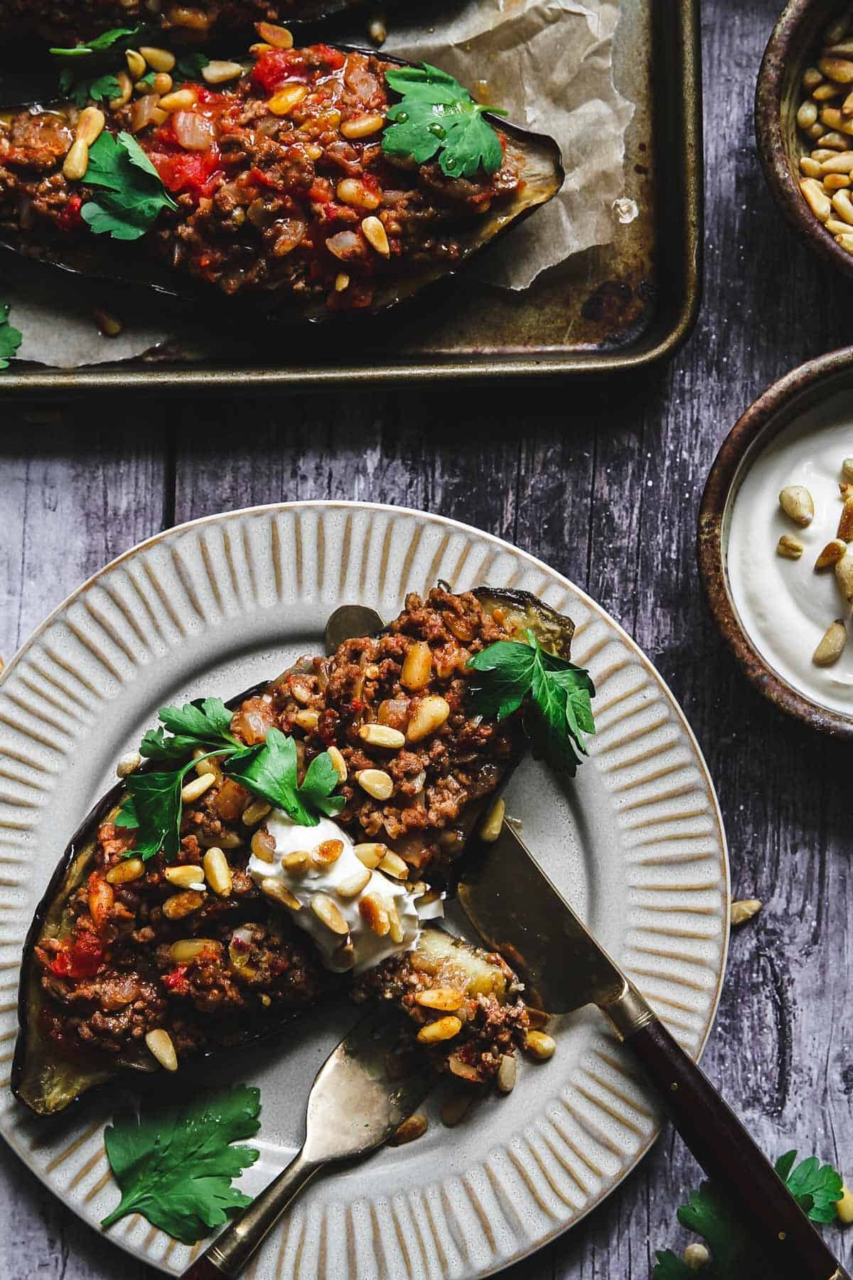 Roasted eggplant half stuffed with ground lamb and pine nuts topped with sour cream and parsley on a white plate.