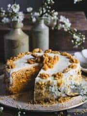 Carrot cake cheesecake on a cake stand with one slice removed.