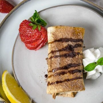 Chimichanga on a plate with chocolate drizzle, lemon, whipped cream, and strawberry.