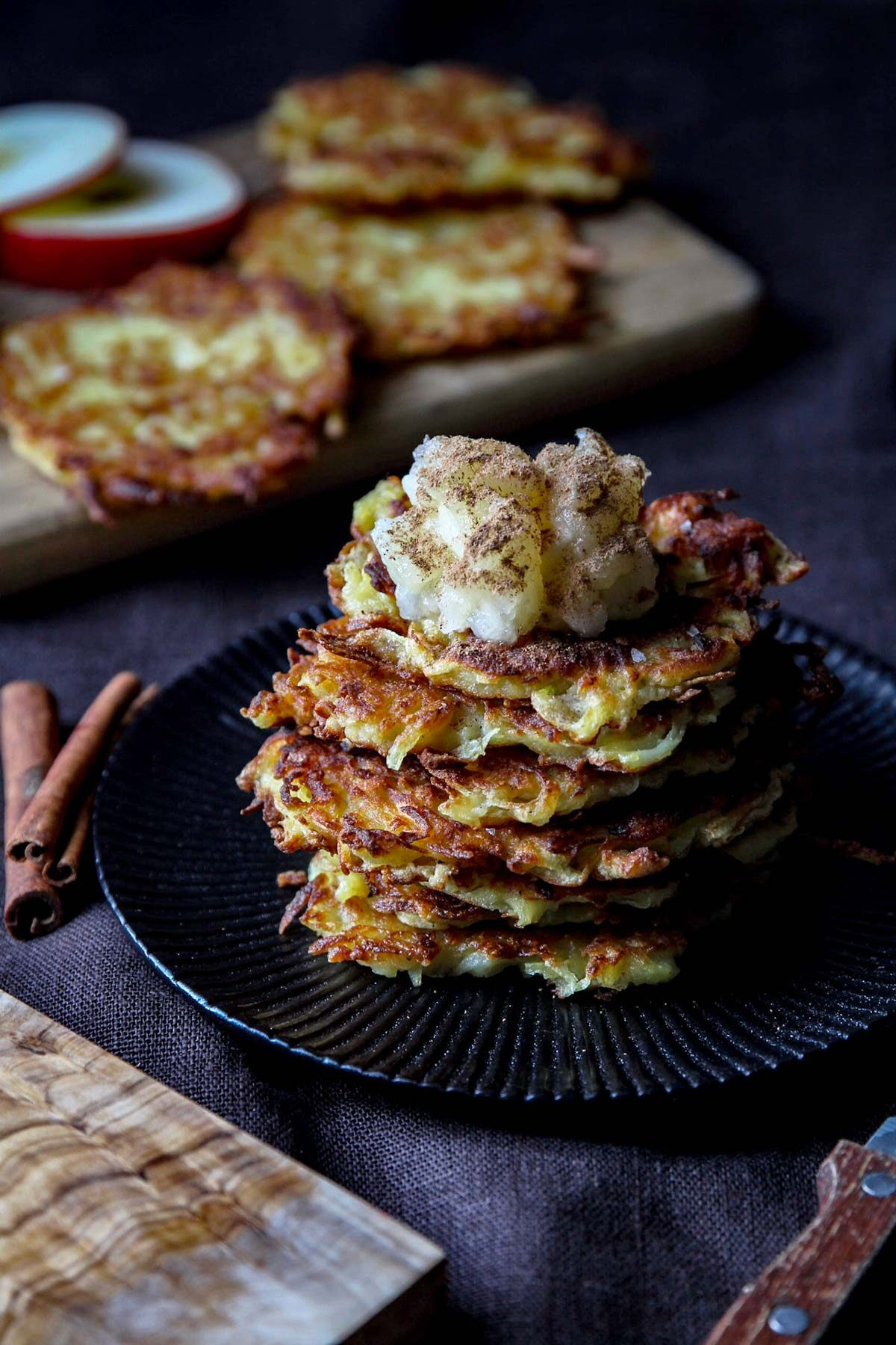 A stack of potato fritters on a plate, topped with applesauce.
