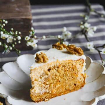 A close up of a carrot cake cheesecake slice on a white plate.