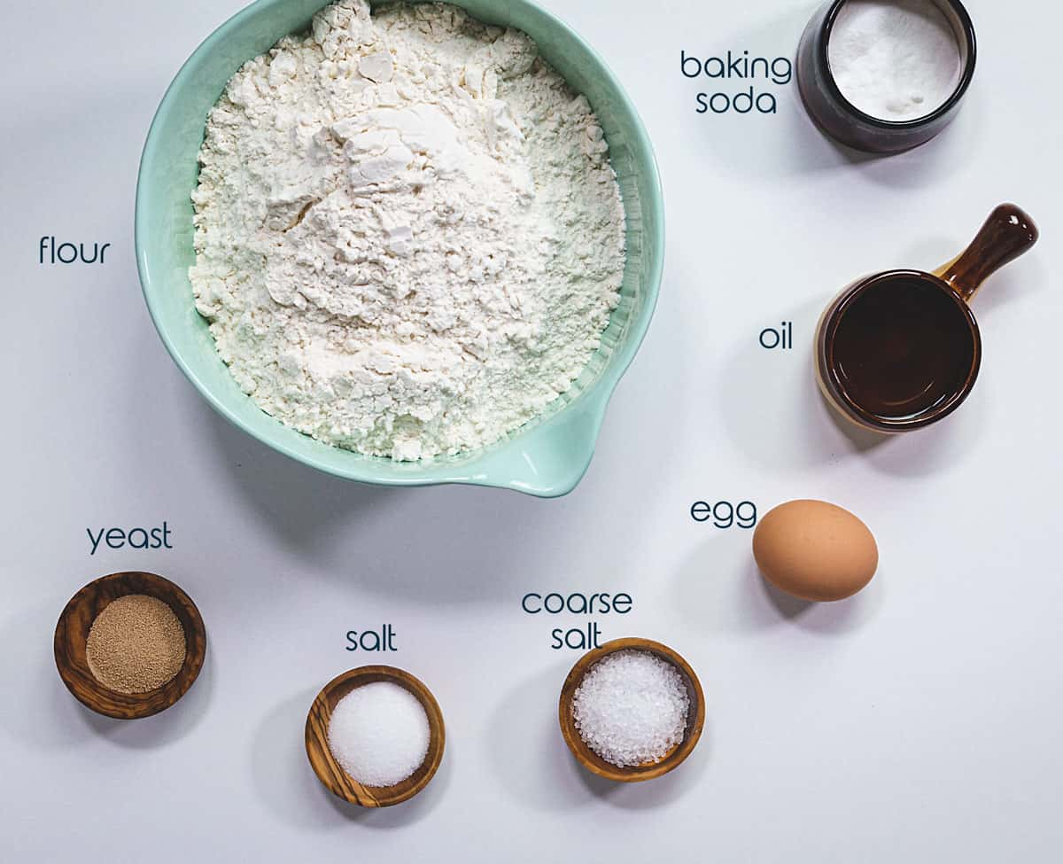 Ingredients for pretzel rolls on a table with flour, yeast, salt, egg, and baking soda.