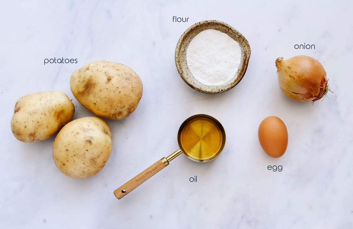 Ingredients for potato pancakes with onion, egg, and flour, on a counter.