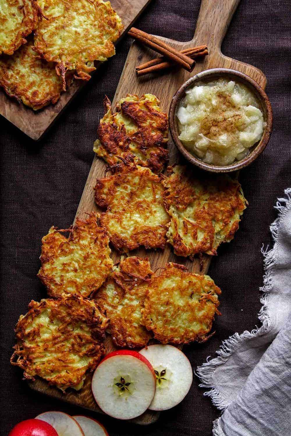 Potato pancakes on a wooden board in a single layer with applesauce.