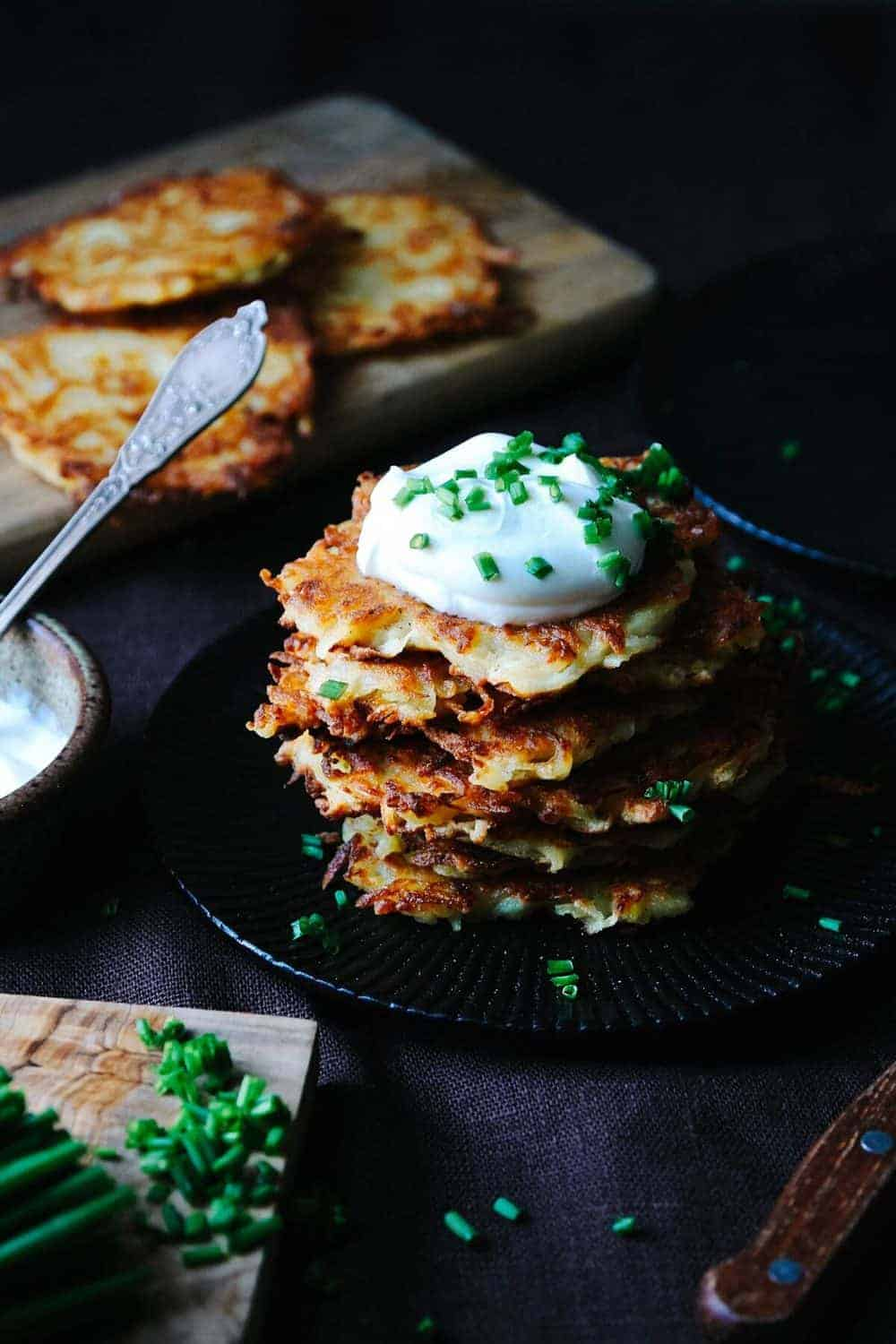 A stack of Kartoffelpuffer on a black plate, topped with sour cream and chives.