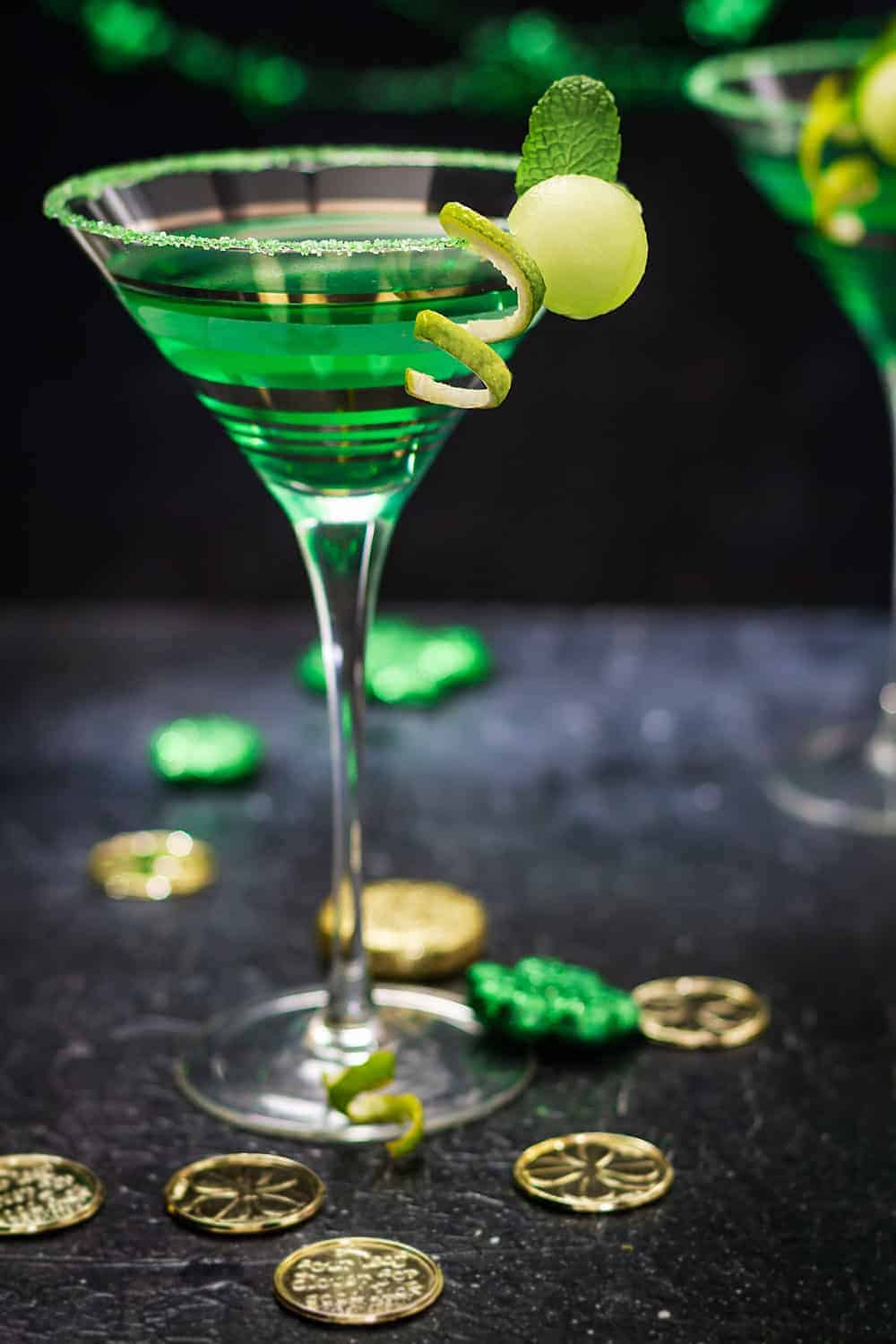 One martini glass with green martini on a black table with Irish decorations.