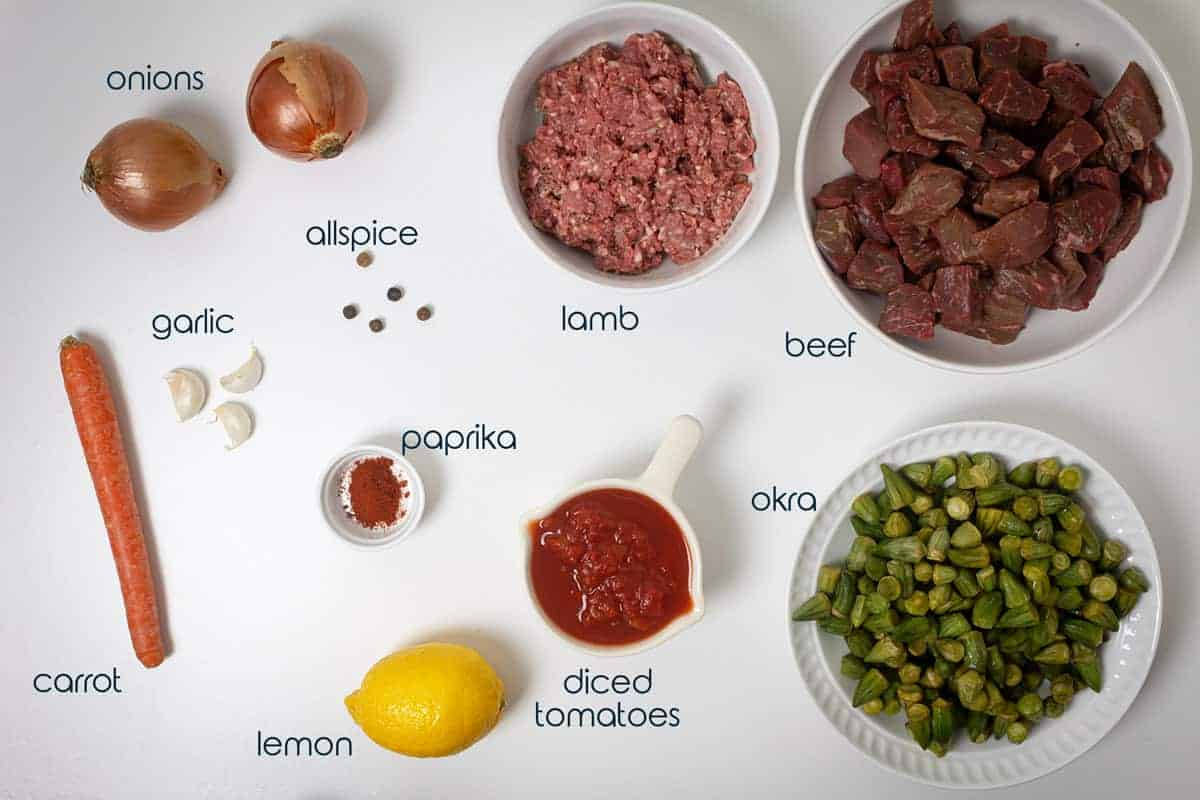Ingredients for okra stew on a counter with lamb, beef, and vegetables, including text.