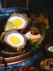 Scotch egg halves in an oval tray with lemon wedges and hot pepper rings.